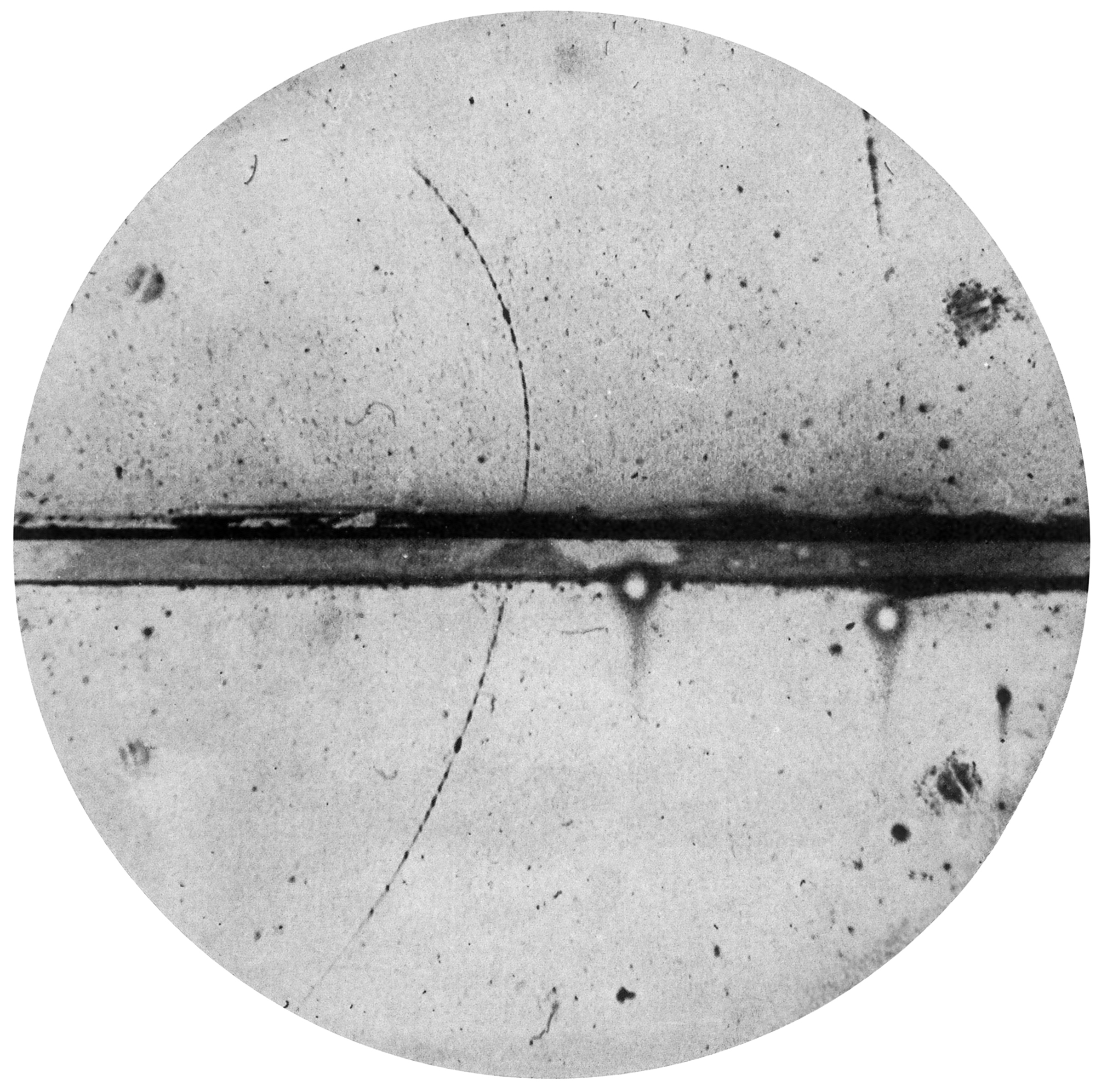 Anderson's picture of a positron's path. It passed through a lead plate (center) and curved to the left, indicating it had a + charge